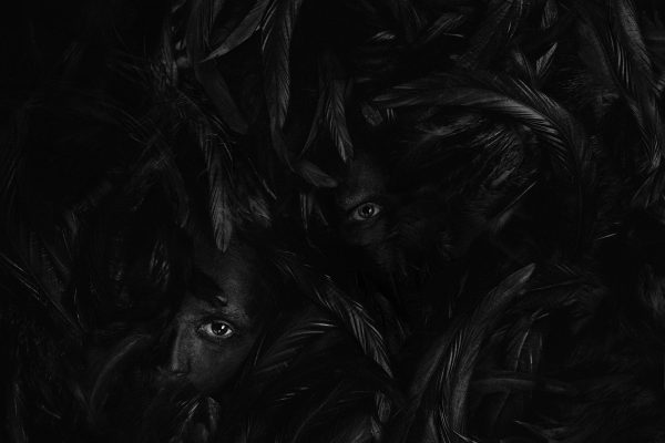 "Black faces lost in a sea of black feathers. Photograph by Greta Do called ""Silence"""""