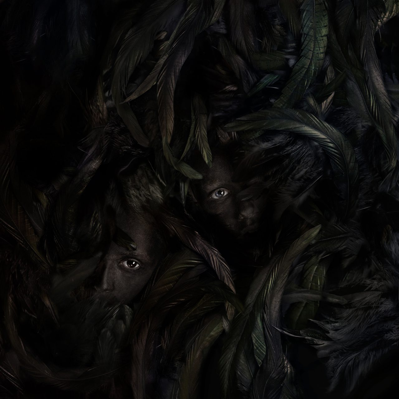 """Black faces in a sea of black feathers. Photo by Greta Do. Titled """"silence""""."""
