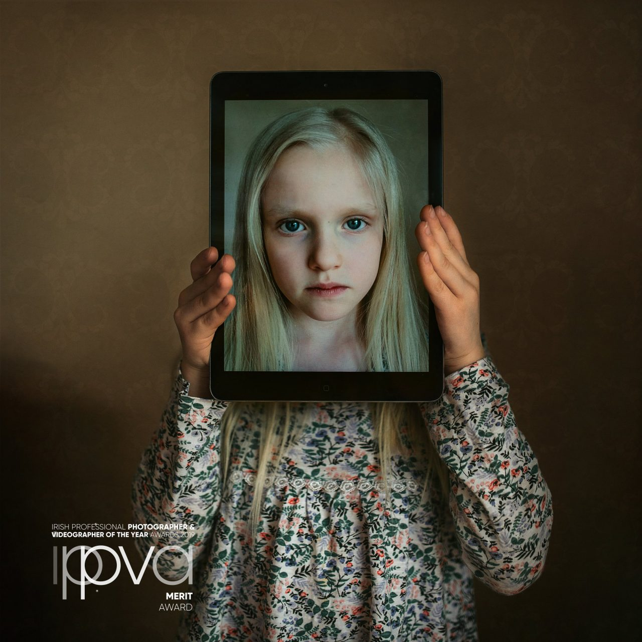 A girl holding a tablet in front of her face. Photo by Greta Do.