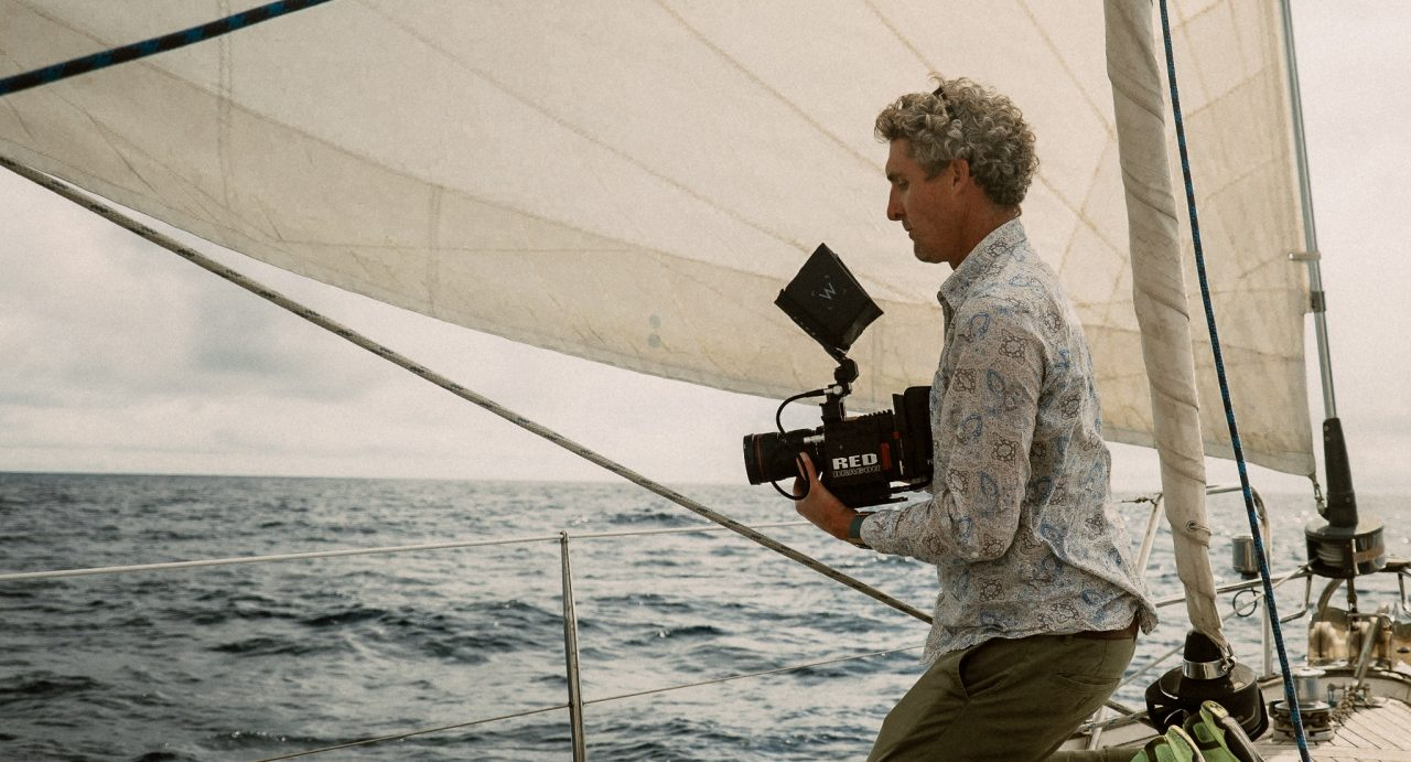Photo of IPPVA videographer Gavin Gallagher filming a documentary series from a boat