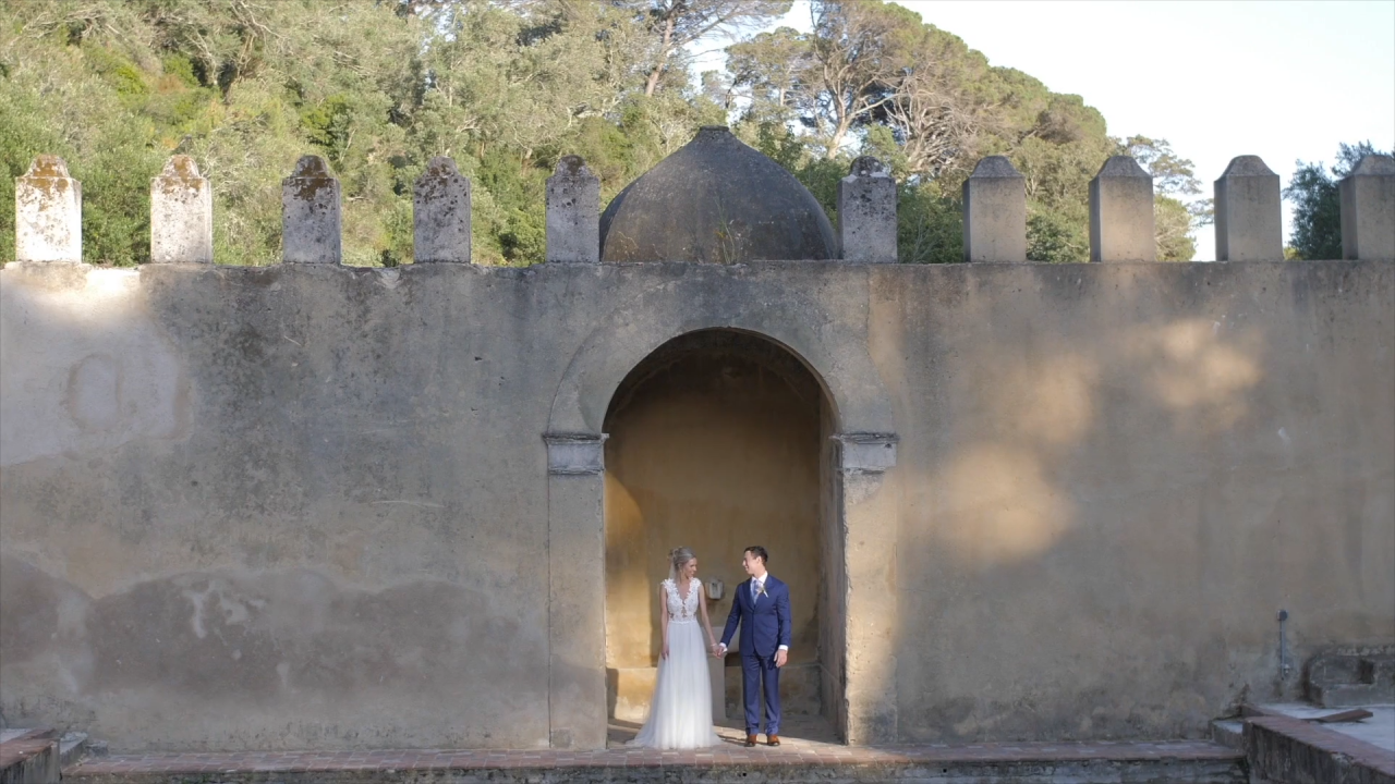 wide angle shot of bride and groom standing under old stone wall in Lisbon
