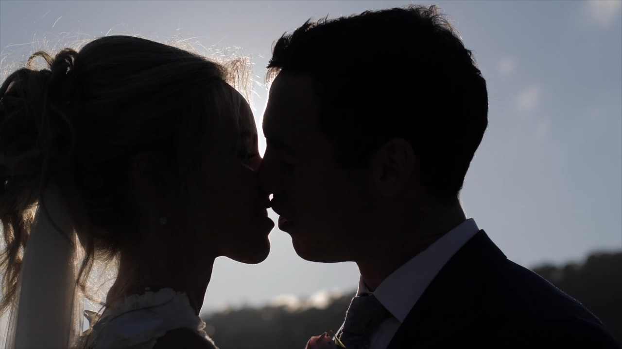 Silhouette cloes-up shot of a bride and groom kissing