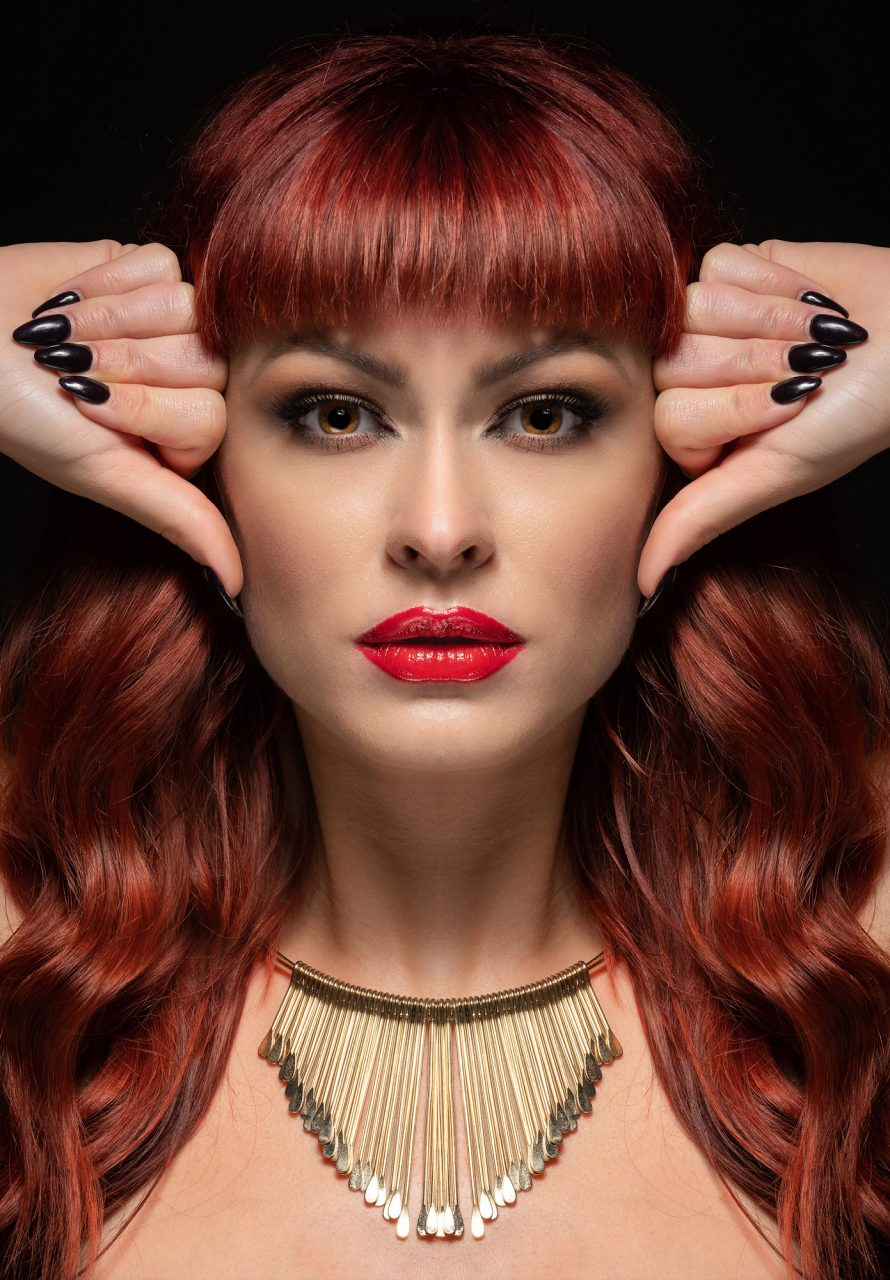 Portrait of a model with red lipstick and hair and black nails - Silver Award in Commercial Photography by Michael Hayes