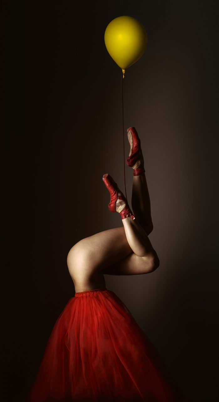 Ballet dancer upside down with legs up and yellow balloon  - Silver Award in Fine Art Photography by Michael Hayes