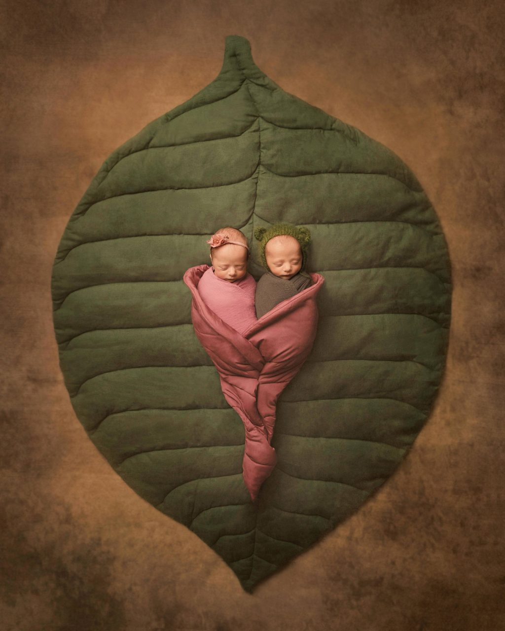 two newborn babies swaddled and asleep next to each other on larger green and soft blanket shaped like a leaf