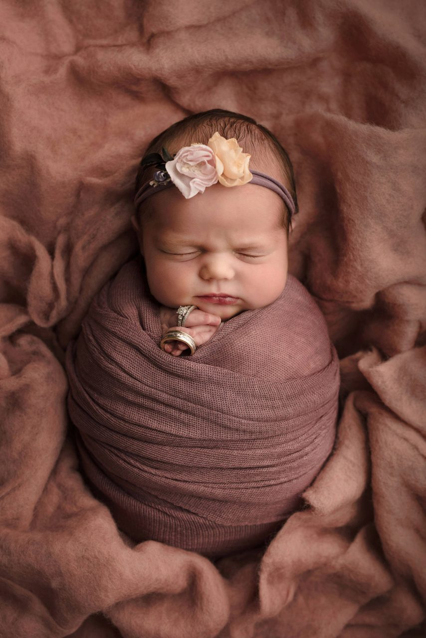newborn baby swaddled in rose-pink blanket and holding two wedding band in their hands