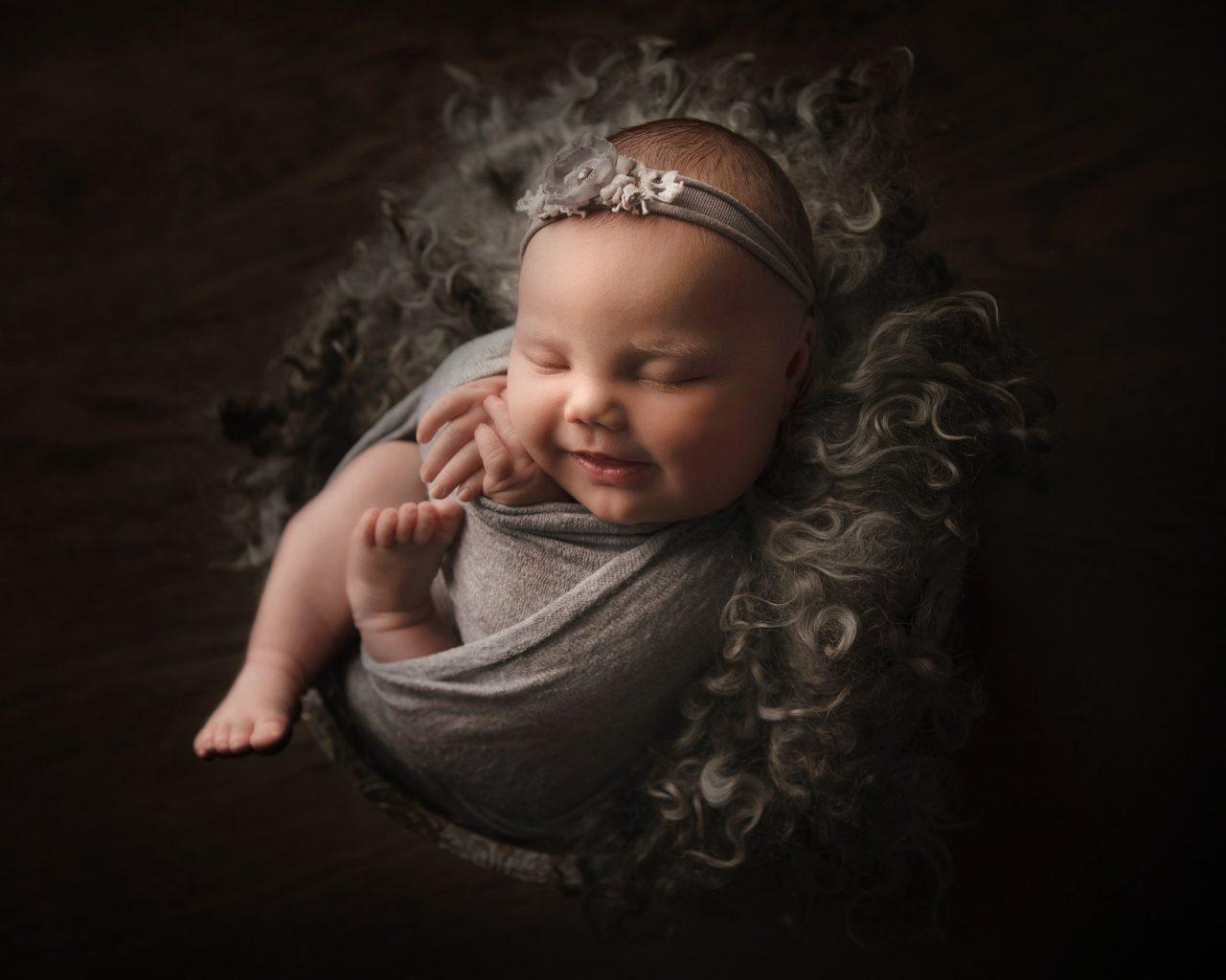 smiling newborn on fluffy blanket