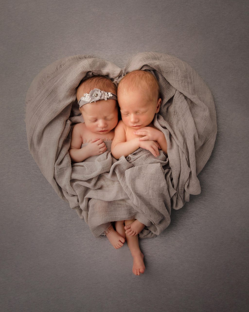 two newborn babies next to each other and wrapped in a blanket which is laid out in the shape of a heart