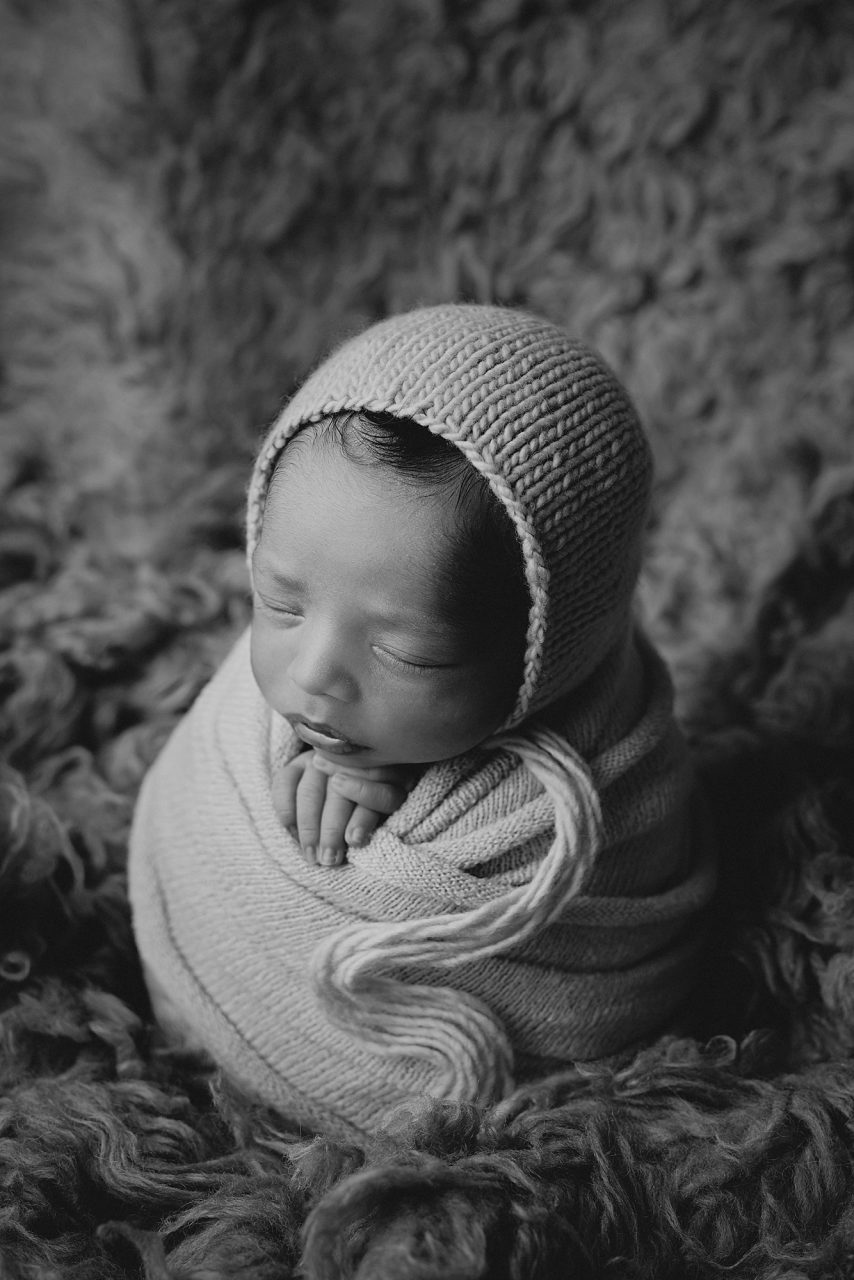 black and white image of a very small newborn baby swaddled in a blanket and in an upright position