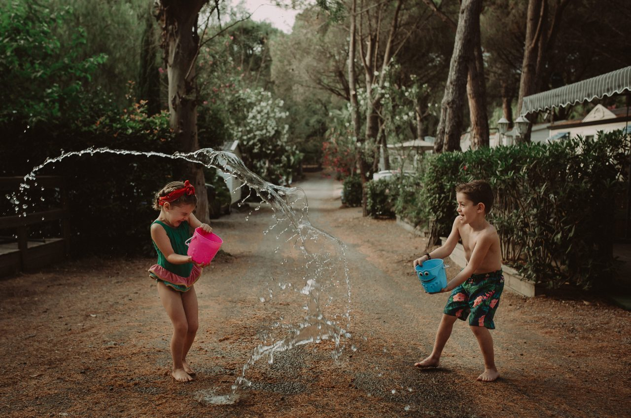 Two children play on a small, tree-lined road. They are in swimming clothes and are throwing water at each other with buckets. The movement of the water is frozen in mid air.