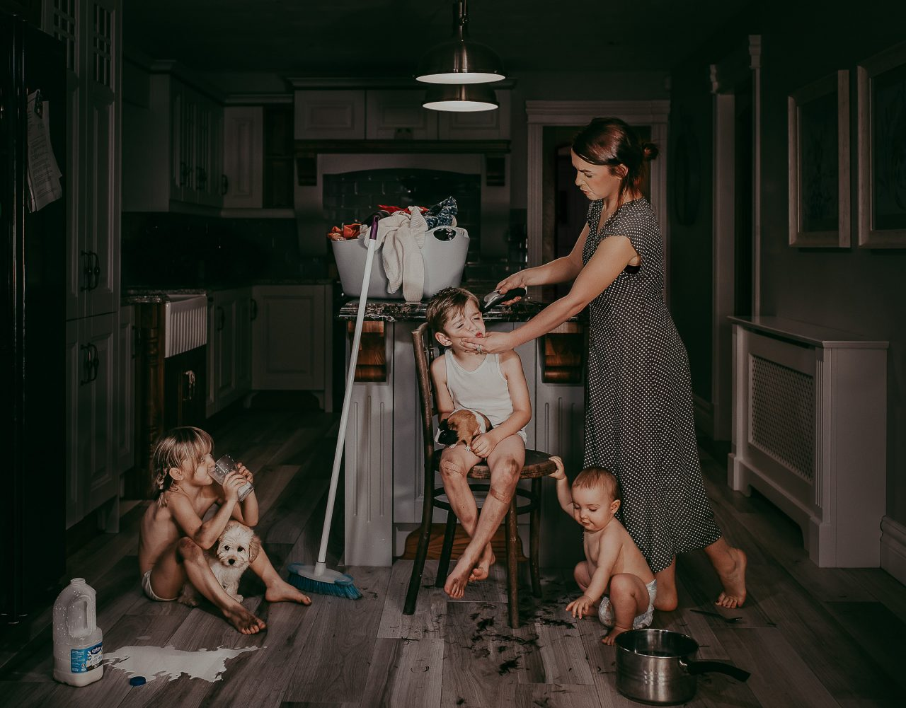 Kitchen scene of a mother and her three small children. The youngest two are sat on the ground while the eldest, a boy, sits on a chair as the mother cuts his hair with an electric trimmer.