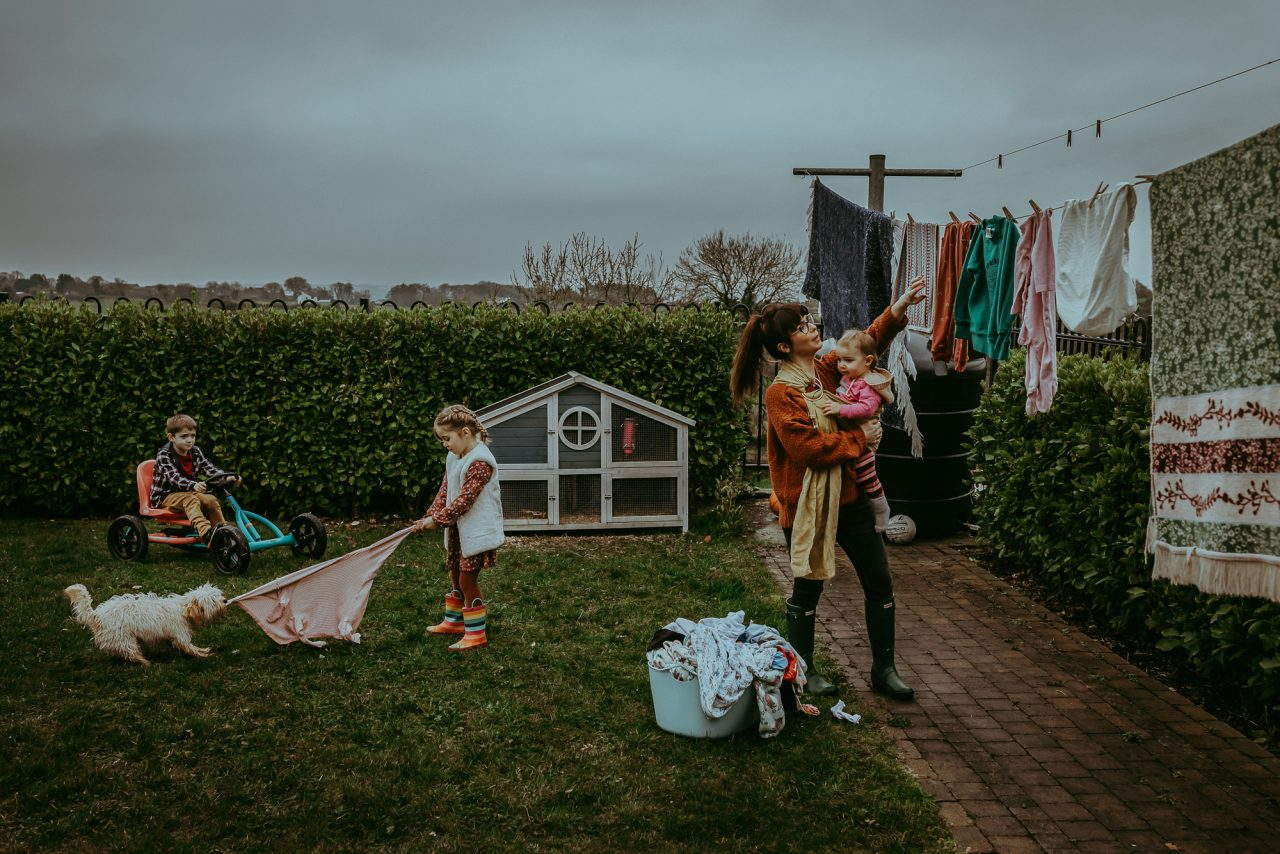 A woman holding a toddler takes clothes off the washing line in a back yard garden surrounded by hedging. Two other children are playing on the grass with a dog