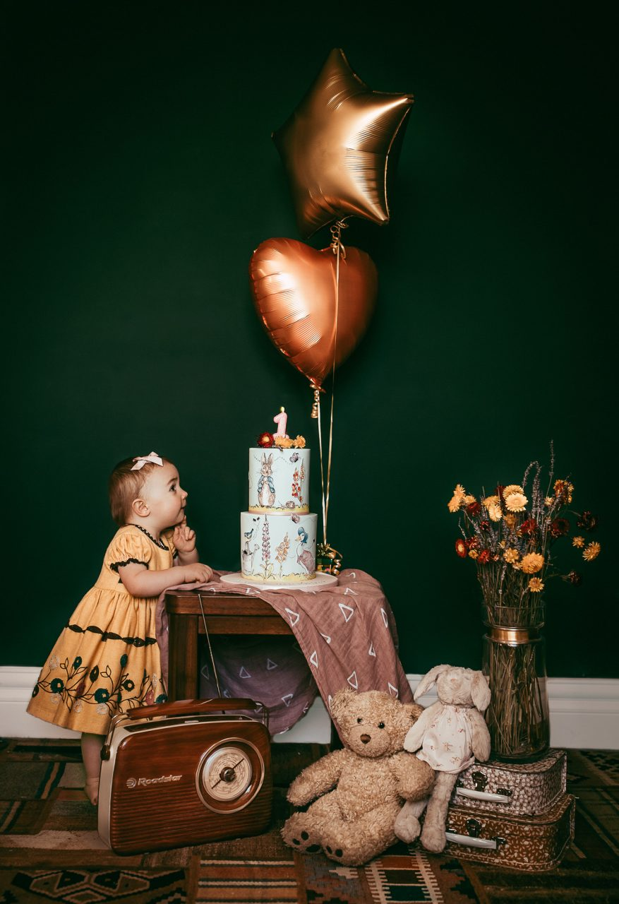 a toddler poses next to a small table with a birthday cake and helium balloons.