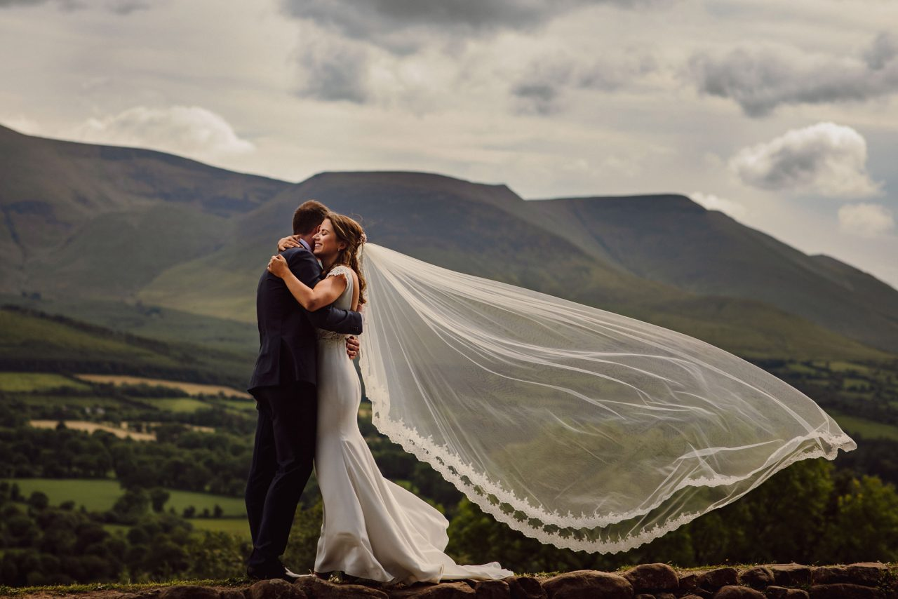 bride and groom embrace, outside on an overcast day with lush green hill in the background. The bride vail appears to be flowing with the wind
