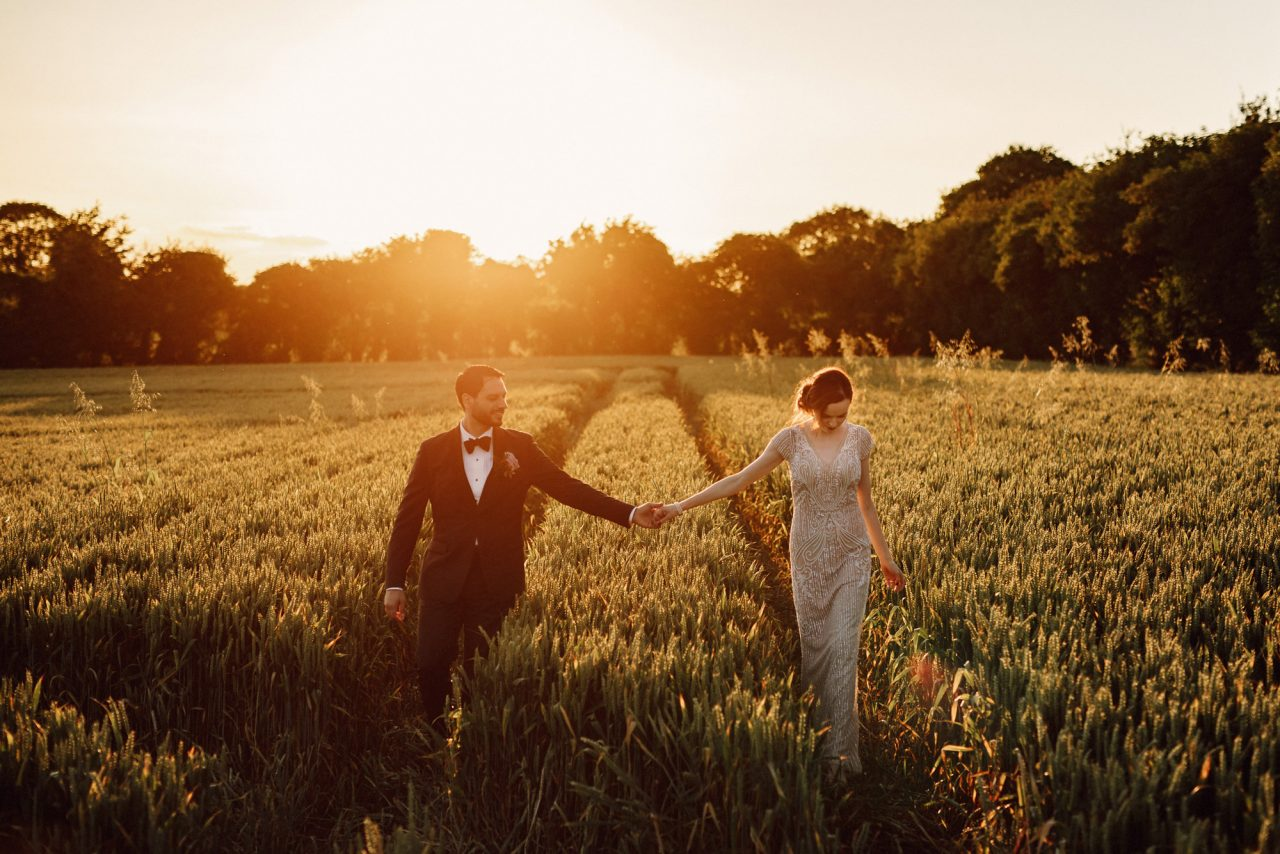 a bride and groom hold hands as they walk down the tracks in a wheat field as the sun sets behind them