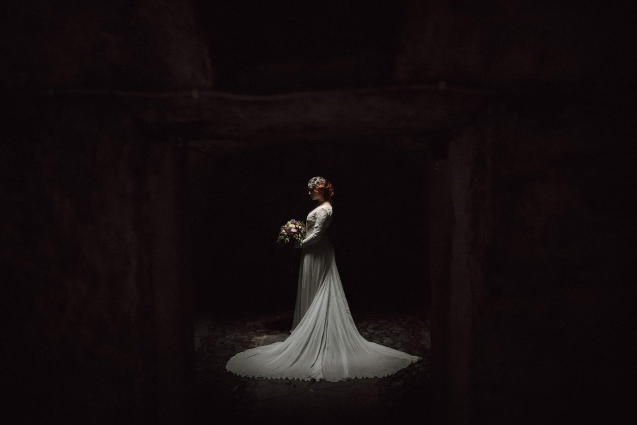 dark image with faint light falling on a woman in a wedding dress, posed with flowers and in the center of the image