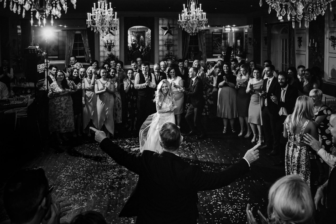 bride and groom dance apart from each other during the first dace at a wedding reception. They are surrounded by a cheerful crowd who are watching them