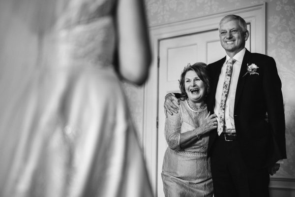 a bride, with her back to the camera, faces her joyful parents, who are embracing while they look at her