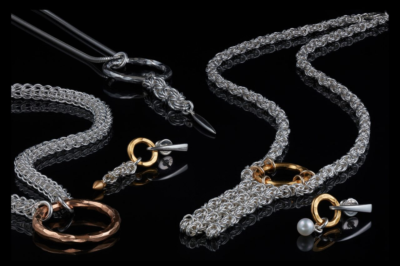 silver chainmail jewelry with golden rings on a black, reflective surface