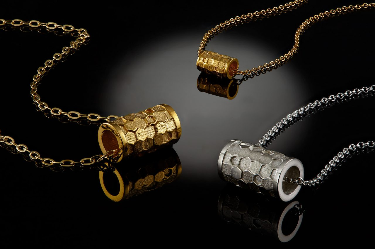 gold and silver necklaces on a black reflective surface