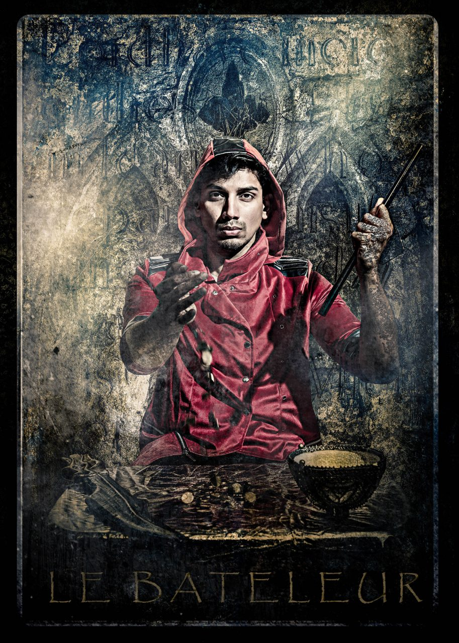 photographic recreation of the tarot card, Le Bateleur, also known as The Magician. A man in a red coat is sitting in at a table, facing the camera and gesturing to the viewer