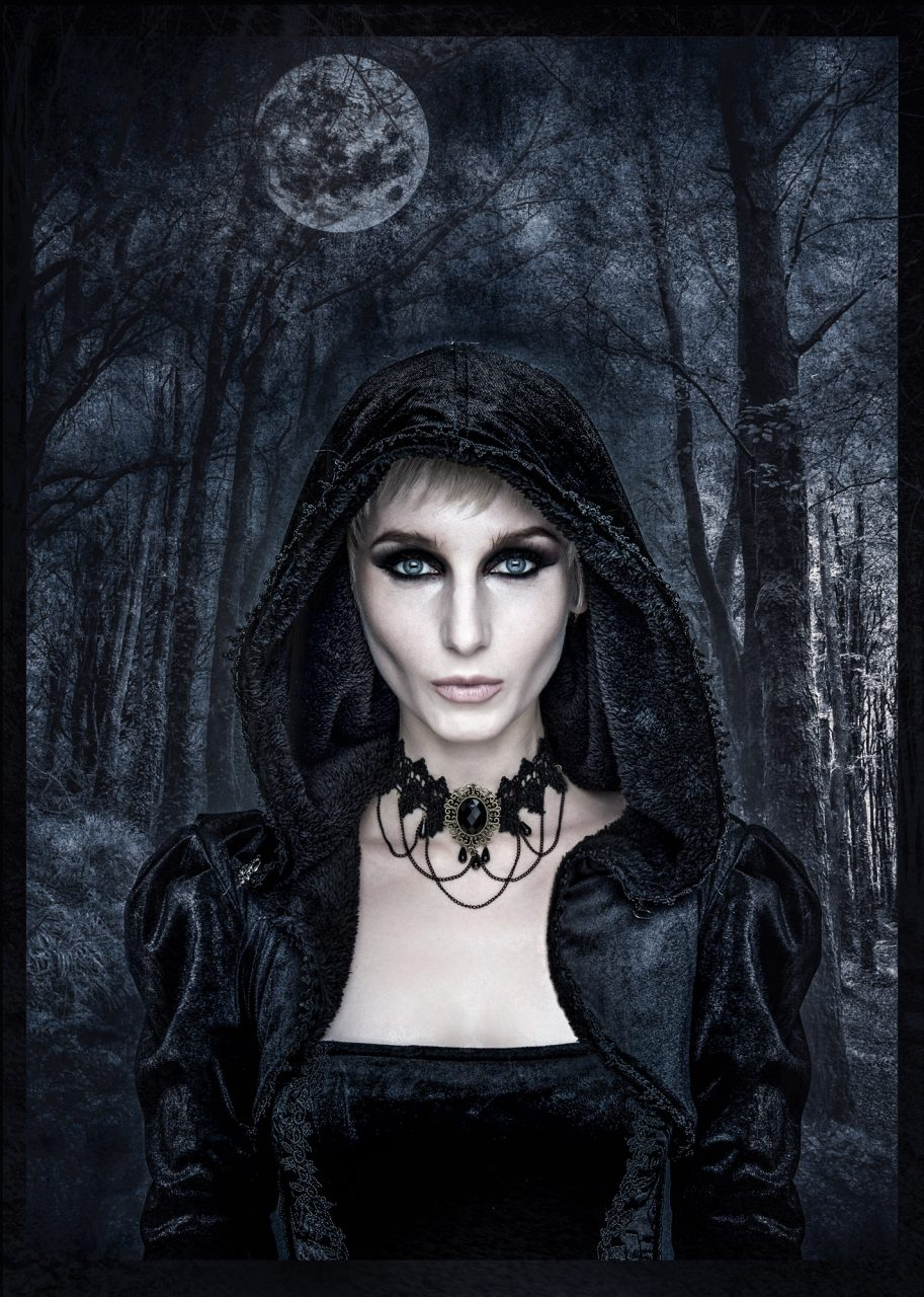 dark image of a pale-faced woman wearing a gothic hooded garb. A full moon can be seen through the dark trees in the background. She's staring at the viewer
