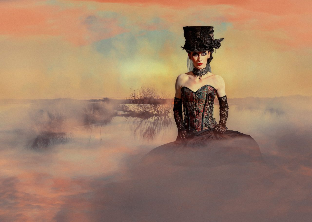 surreal image of a woman in a Victorian dress, outside, surrounded by colourful mist and fog