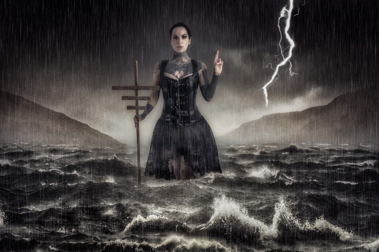 fine art image of a woman in a Victorian dress surrounded by choppy waters and a stormy sky. She's holding a staff and has her left hand raised