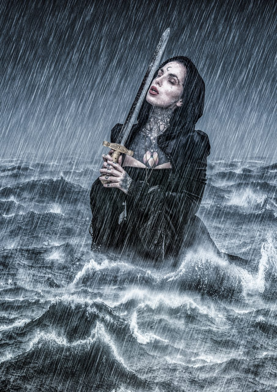 Woman in stormy sea holding a sword to her face