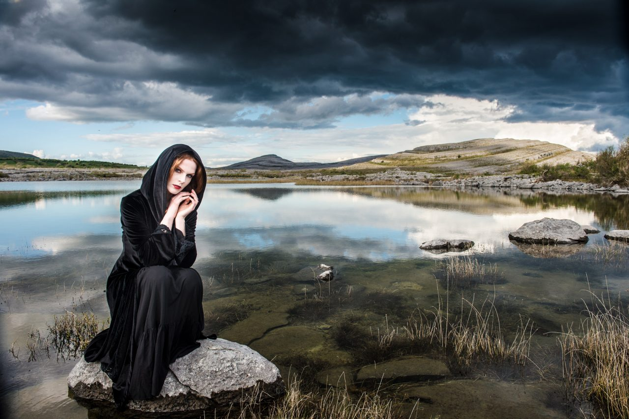 woman in black sitting on a small rock at the edge of a lake with rocky hills in the background