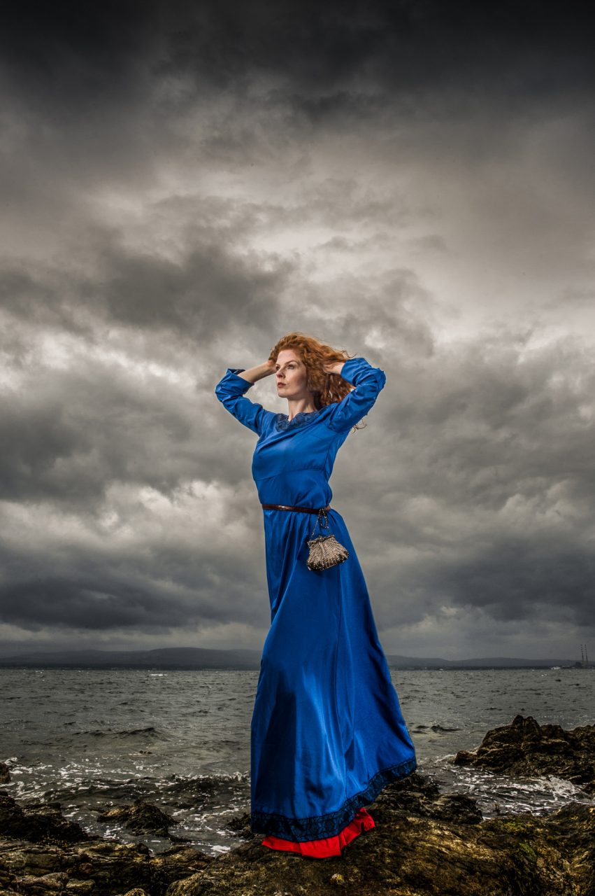 woman with red, wavy hair in a blue medieval-style dress. She's on a rocky shore with dark skies in the background