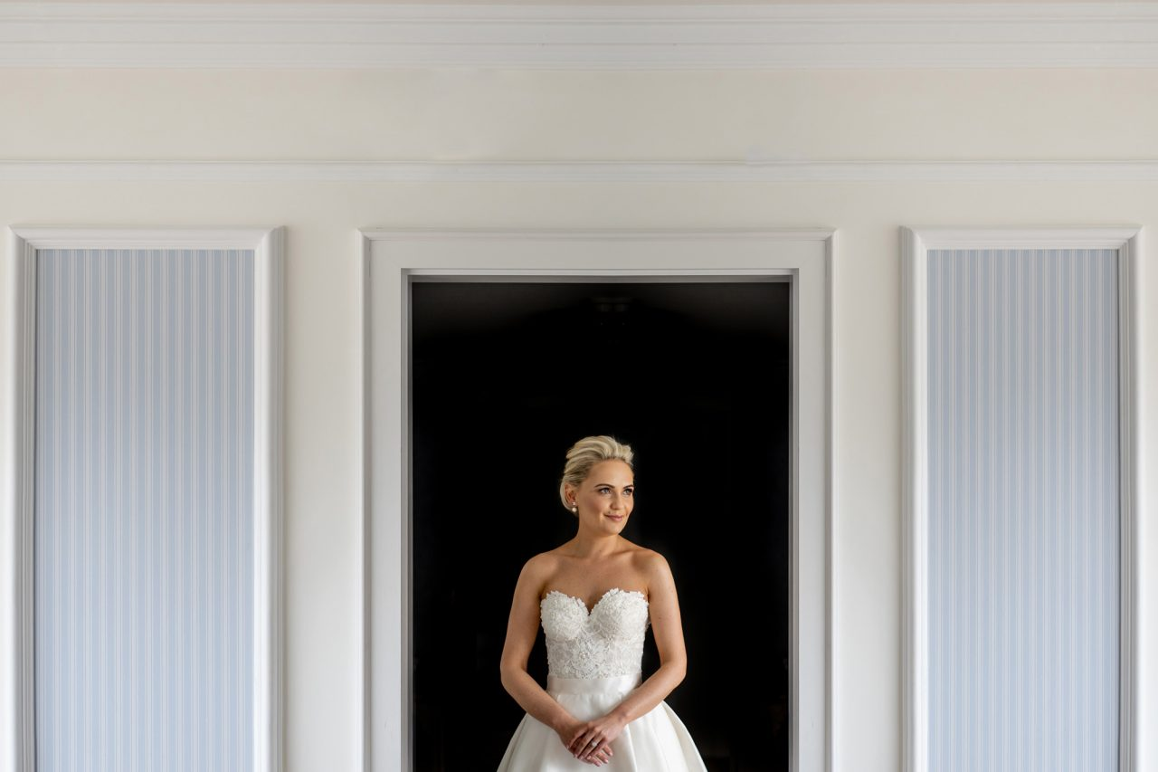 A smilling Bride in her wedding dress stands in a white room with classic wall moldings. She is framed by an empty, dark doorway behind her so she really stands out