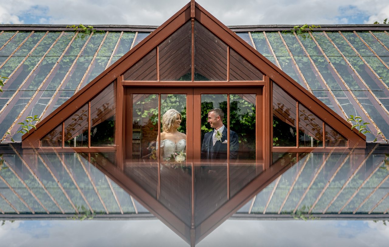 bride and groom standing inside a wood-framed greenhouse door, looking and smiling at each other. There is a reflection of the scene in the foreground