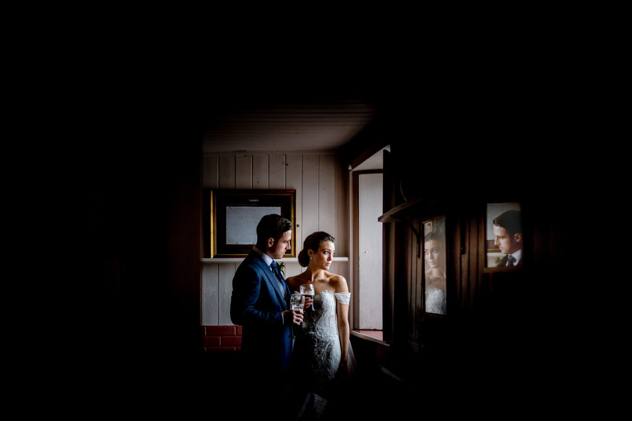 bride and groom stand by a bright window in a dimly-lit pub, holding tow half-drank pints of Guinness. Their faces are reflected in, and framed by, two picture frames in the foreground