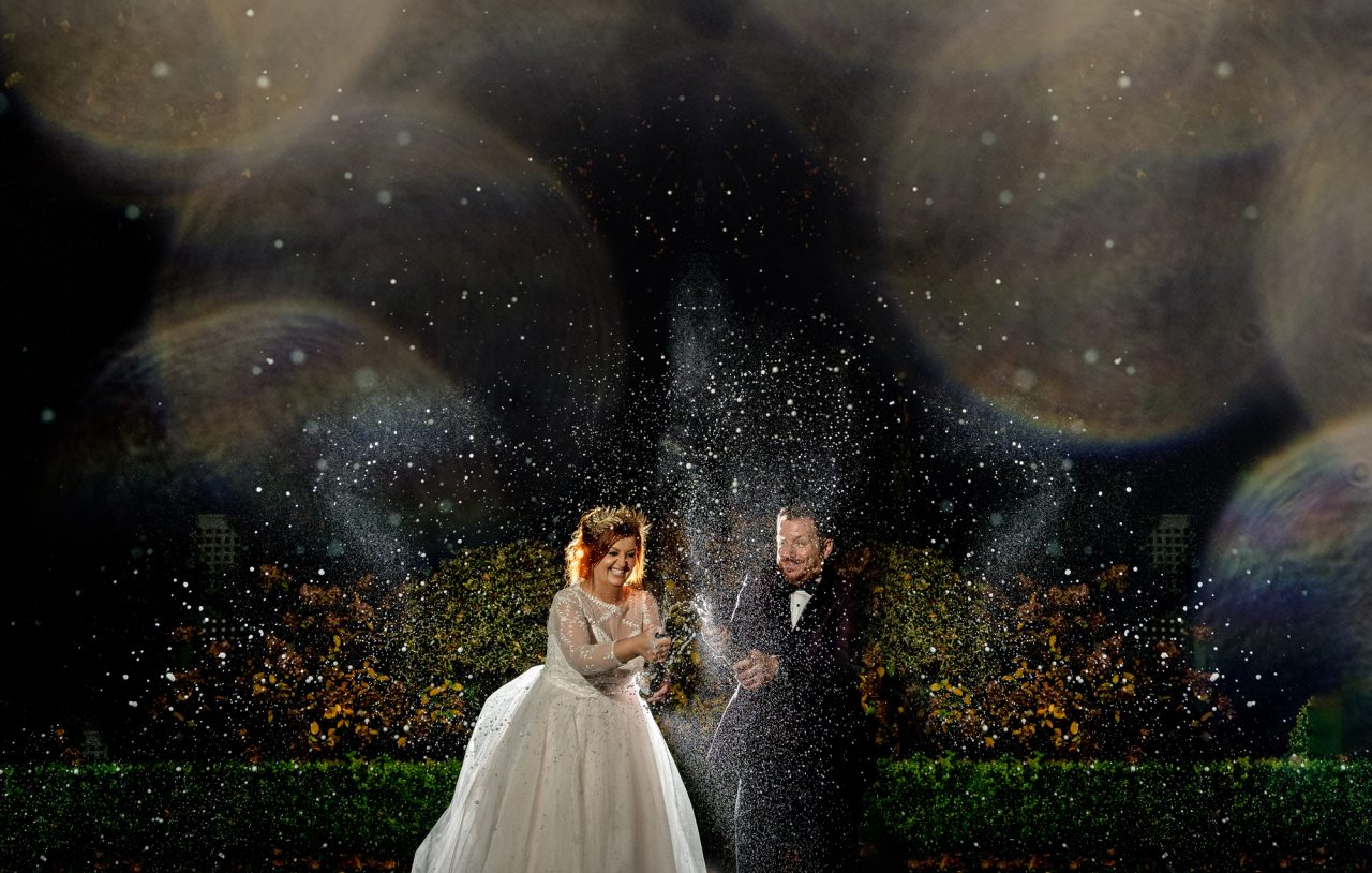 A joyful bride and groom crack open a bottle of champagne outside at night