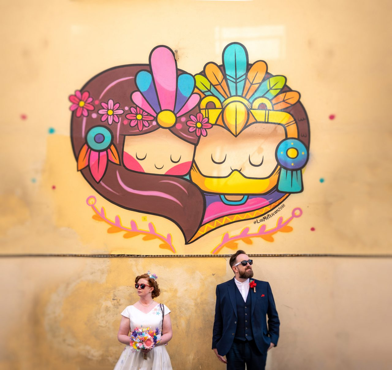 Bride and Groom pose in fron of a wall with cartoon-style graffiti of a couple