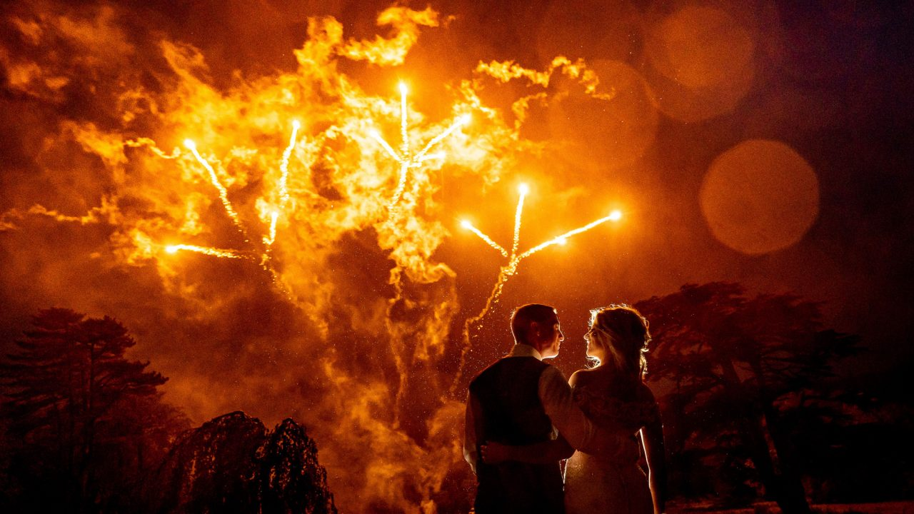 Bride and Groom stand looking at each other but with their backs to the camera as amber fireworks go off in the sky in the background