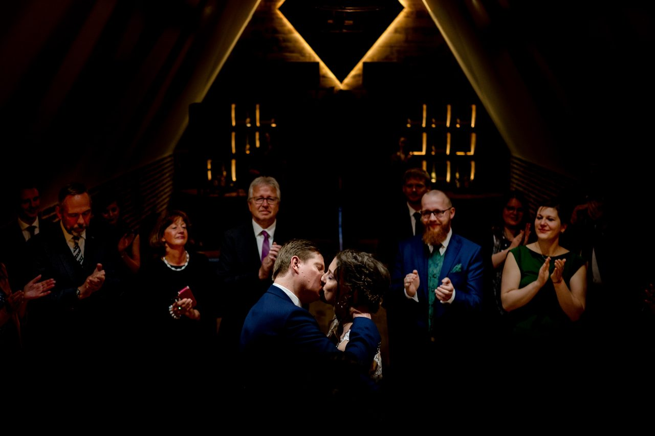 Bride and groom kiss while surrounded by applauding guests in a dimly-lit, intimate chapel
