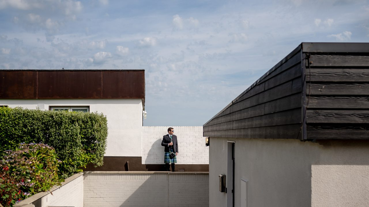 architectural image of a Groom in a traditional kilt, standing against a white brick wall and holding a half-drank pint. The light from the sun is harsh and he is framed by a building in the left foreground and shrubs on the left