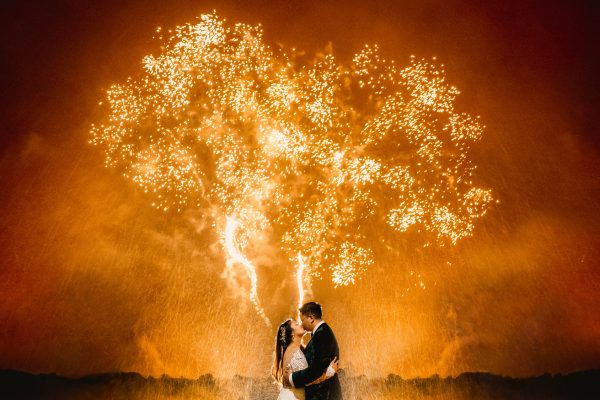 bride and groom kissing in front of amber fireworks