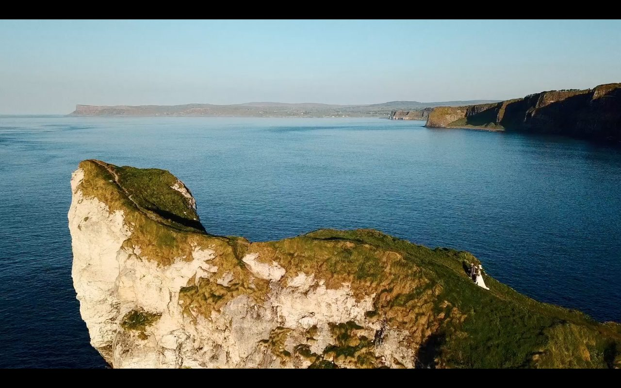 Still of a wedding film showing bride and groom walking up a scenic cliff location in Northern Ireland.