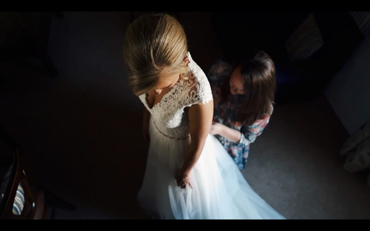 Still of a wedding film showing bride getting help from her bridesmaid to get ready for her wedding elopement in Northern Ireland