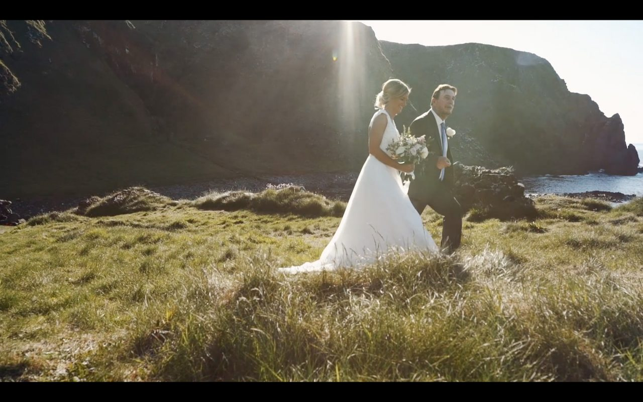 Still of a wedding film showing Bride and her father walking towards the groom during wedding elopement in Northern Ireland