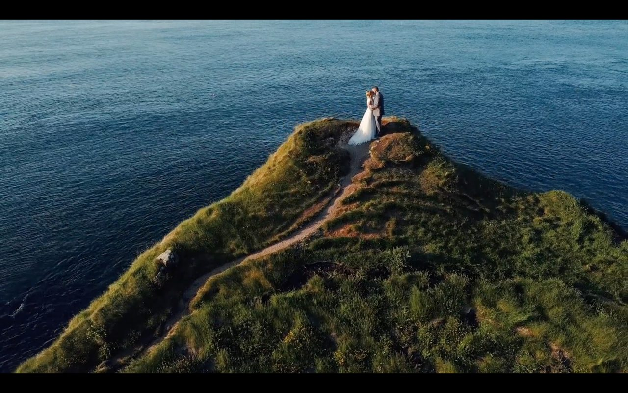 Still of a wedding film showing bride and groom kissing on top of a cliff location in Northern Ireland