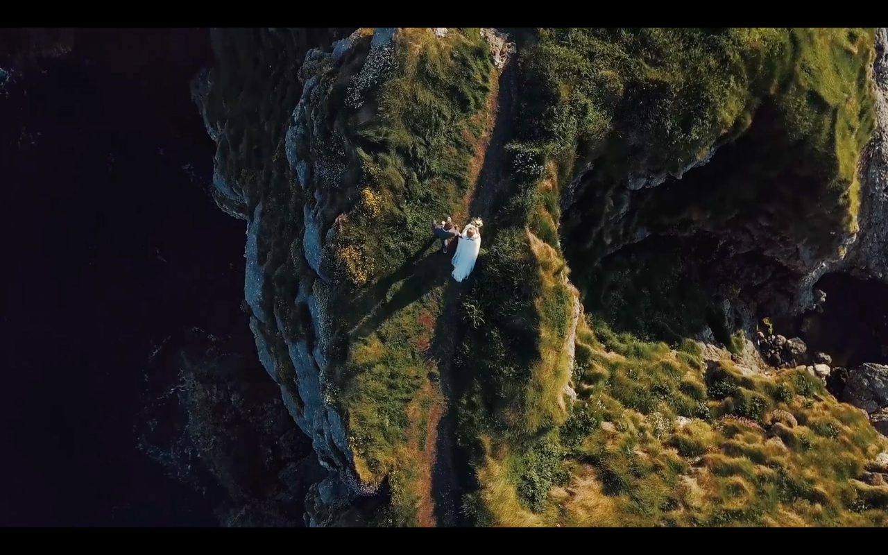 Wedding film Drone still of a bride and groom walking on cliff location in Northern Ireland during their elopement
