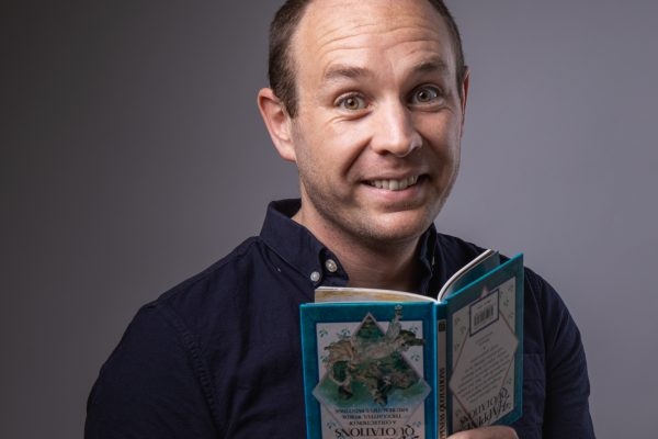 portrait of a smiling man holding open an upside-down book