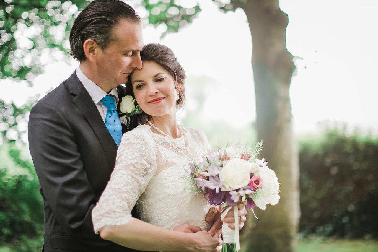 groom embracing his bride from behind