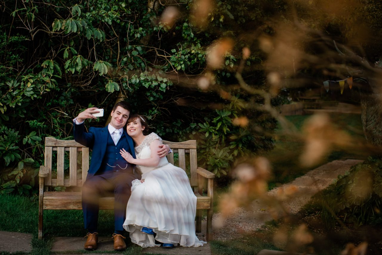bride and groom sitting on a bench taking a selfie