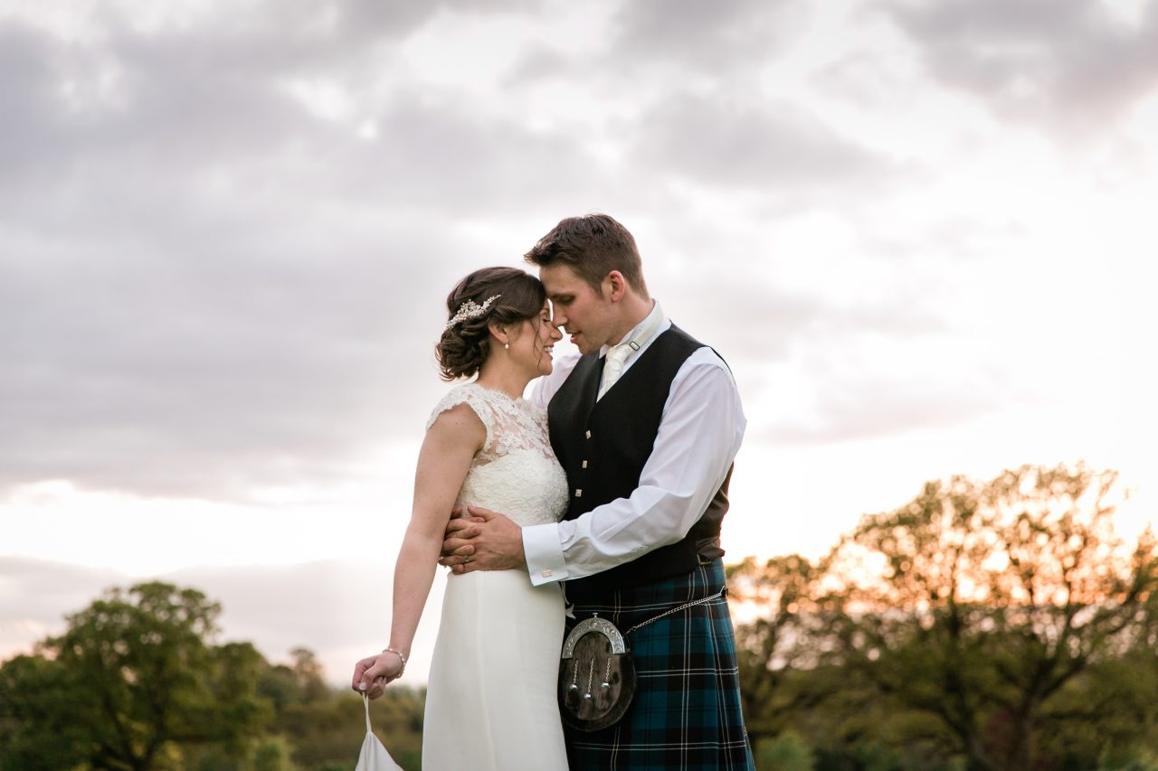 Bride and groom embracing in front of a sunset