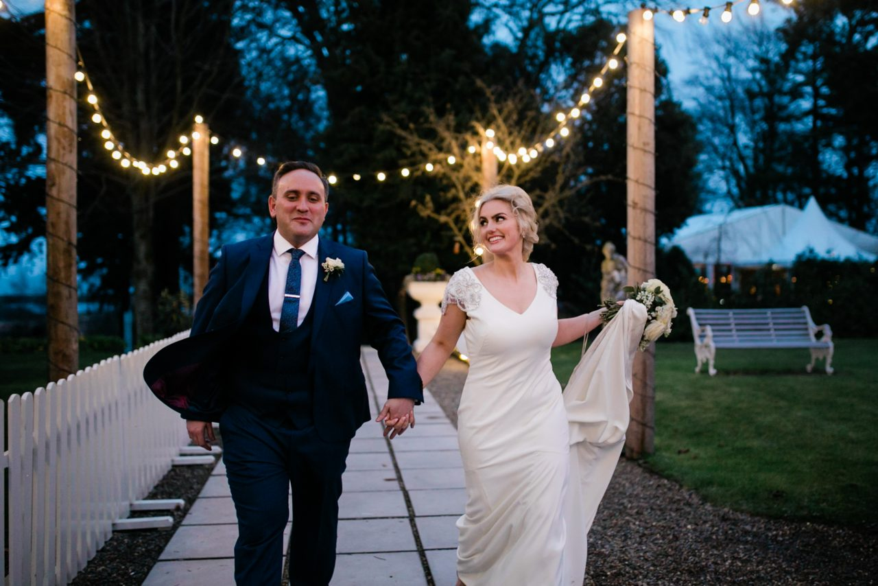 Bride and groom running through courtyard at night
